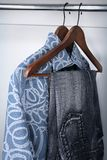 Blue jeans and shirts on wooden hangers. In a closet royalty free stock images