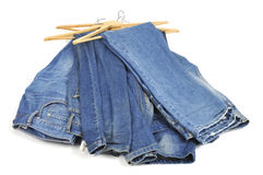 Blue jeans. Some blue jeans in wooden clothes hangers on a white background royalty free stock photo