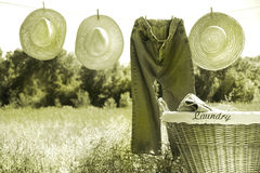 Blue jeans and straw hats on clothesline Stock Images