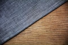 Blue jeans texture on wood background. Wood background on blue jeans texture stock images