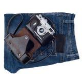 Blue Jeans und eine alte Kamera lokalisiert auf weißem Hintergrund Lizenzfreie Stockfotos