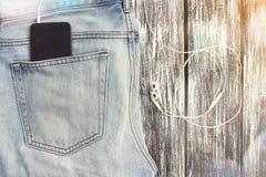 Blue Jeans und Kopfhörer mit Ihrem Smartphone in der Tasche Lizenzfreie Stockbilder