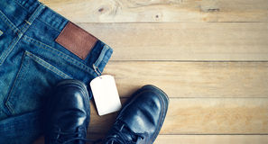 Blue jeans with white blank tag and shoes on wooden background. Blank text Stock Photo