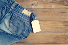 Blue jeans with white blank tag on wooden background. Blue jeans with white blank tag on wooden table  background Stock Photography
