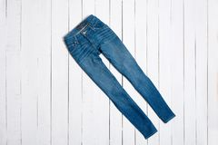 Blue jeans on white wooden background. Fashion concept.  stock photo