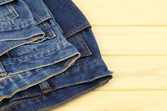 Blue jeans on wooden background Stock Photos