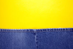Blue jeans with yellow background Stock Images