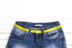 Blue jeans with yellow measure tape instead of belt on white woo. Den background. Weight loss, dieting and healthy concept royalty free stock photography