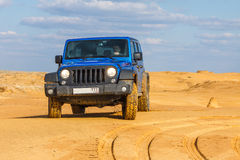 Blue Jeep Wrangler Rubicon Unlimited at desert sand dunes Stock Photos
