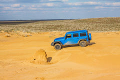 Blue Jeep Wrangler Rubicon Unlimited at desert sand dunes Stock Images