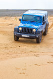 Blue Jeep Wrangler Rubicon Unlimited at desert sand dunes Royalty Free Stock Images