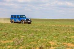 Blue Jeep Wrangler Rubicon Unlimited in steppe near Utta village. Stock Image