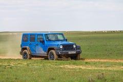 Blue Jeep Wrangler Rubicon Unlimited in steppe near Utta village. Stock Photos