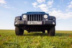 Blue Jeep Wrangler Rubicon Unlimited in wild tulip field near saltwater reservoir lake Manych-Gudilo Stock Photo