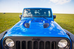 Blue Jeep Wrangler Rubicon Unlimited in wild tulip field near saltwater reservoir lake Manych-Gudilo Royalty Free Stock Photography