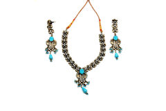 Blue Jewelery Set. An ethnic jewelery set with blue beads and gemstones, on a white fabric background Stock Photo