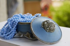 Blue jewelry Box with the silver moldings on the legs,   beads  a string. Close, Royalty Free Stock Images