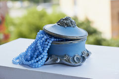 Blue jewelry Box with the silver moldings on the legs,   beads  a string. Close, Royalty Free Stock Photo
