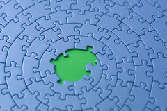 Blue jigsaw with missing pieces in the center. Shallow DOF, focus is on and over the missing pieces - adobe RGB Stock Photography