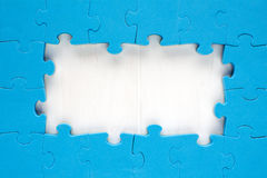 Blue jigsaw puzzle pieces arranged as a border Stock Photos
