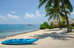 Blue kayak on beach in the tropics Royalty Free Stock Photography