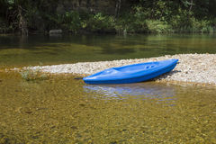Blue Kayak on Gravel Bar. A small blue kayak setting on a gravel bar in the middle of the Jack's Fork River in Missouri.  Crystal clear, slow flowing water Stock Photos