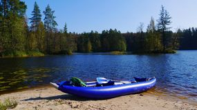 Blue kayak on lake shore. Blue inflatable kayak with green backpack and paddle on the lake shore among forests Royalty Free Stock Photography
