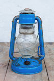 Blue kerosene lantern. Old blue kerosene lantern on the wooden table Stock Images