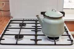 Blue kettle made of steal standing on kitchen gas stove. Royalty Free Stock Images