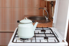 Blue kettle made of steal standing on kitchen gas stove. Royalty Free Stock Image
