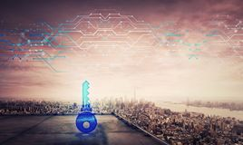 Blue key icon hologram on the rooftop of a skyscraper over the big city sunset horizon, double exposure effect. Private future. Security password cyber attack stock photography