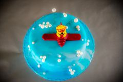Blue kids birthday cake. Decorated with plane toy on grey background Royalty Free Stock Photo