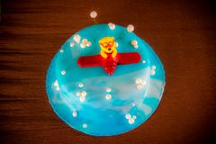 Blue kids birthday cake. Decorated with plane toy on brown background Stock Photos