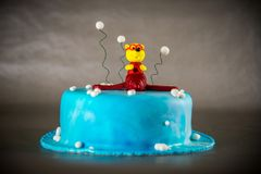 Blue kids birthday cake. Decorated with plane toy on grey background Stock Image