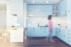 Blue kitchen, white furniture blur. White kitchen interior with a dark wooden floor and blue countertops. A white table with chairs. A woman. 3d rendering mock Royalty Free Stock Photo