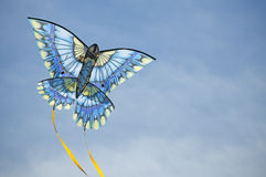 Blue kite arcs across the sky. Blue toned-colored kite flies against a blue sky background with white clouds, yellow streams trailing behind Stock Photo