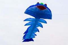 Blue kite that is flying Stock Photos