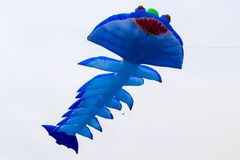 Blue kite that is flying Stock Image