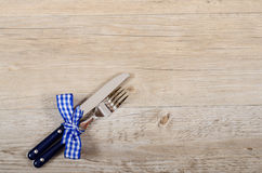 Blue knife and fork with checkered bow on a wooden table Royalty Free Stock Photos