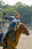 Blue Knight. A knight in armor rounds a corner on horseback on a tournament field while saluting the audience with a standard Royalty Free Stock Photo