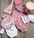 Blue knitted baby clothes with white knitting yarns. Composed on the white table stock image