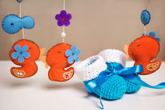 Blue knitted baby shoes with a blue ribbon around toys rattles. Stock Photo