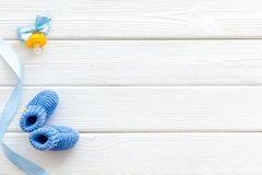 Blue knitted footwear and dummy for baby on white wooden background top view mockup