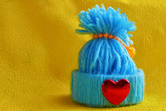 Blue knitted hat with a heart. On a yellow background Royalty Free Stock Image