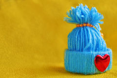 Blue knitted hat with a heart. On a yellow background Royalty Free Stock Photos