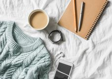 Blue knitted sweater, coffee with milk, notebook, headphones, smart phone on bed, top view. Women clothing. Flat lay Stock Image