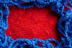 Blue knitted thread on a red fabric background. And space for text Stock Photography