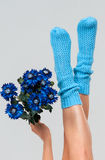 Blue knitted womens socks. Blue knitted women's socks with bouquet on gray background Stock Photos