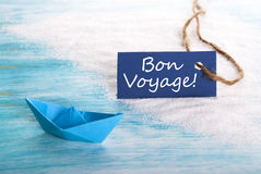 Blue Label with Bon Voyage. A Blue Label with Bon Voyage which means Safe Trip at the Beach with a Boat Royalty Free Stock Photography