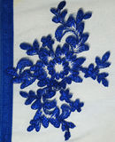 Blue Lace Detail. A dark blue embroidered lace pattern sewn into a fine mesh background Stock Photos